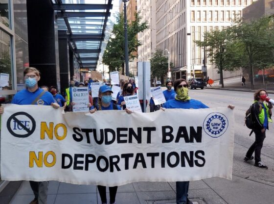 "Protestors carry banner that says ""No student ban, no deportations"""