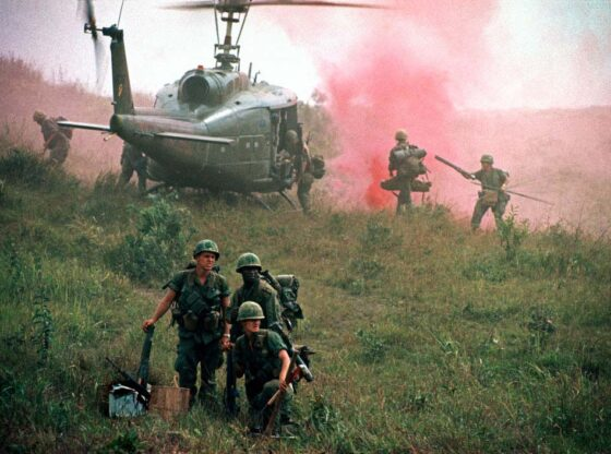 Three soldiers stand in the foreground of a green, grassy field. A helicopter looms in the background, two soldiers beside it, pink aerosol spray emanating just beyond.