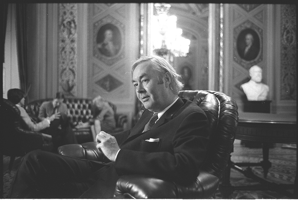 A portrait of Daniel Patrick Moynihan depicts him seated comfortably in a large leather chair, in an ornately decorated sitting room replete with portraits and a bust of white men.