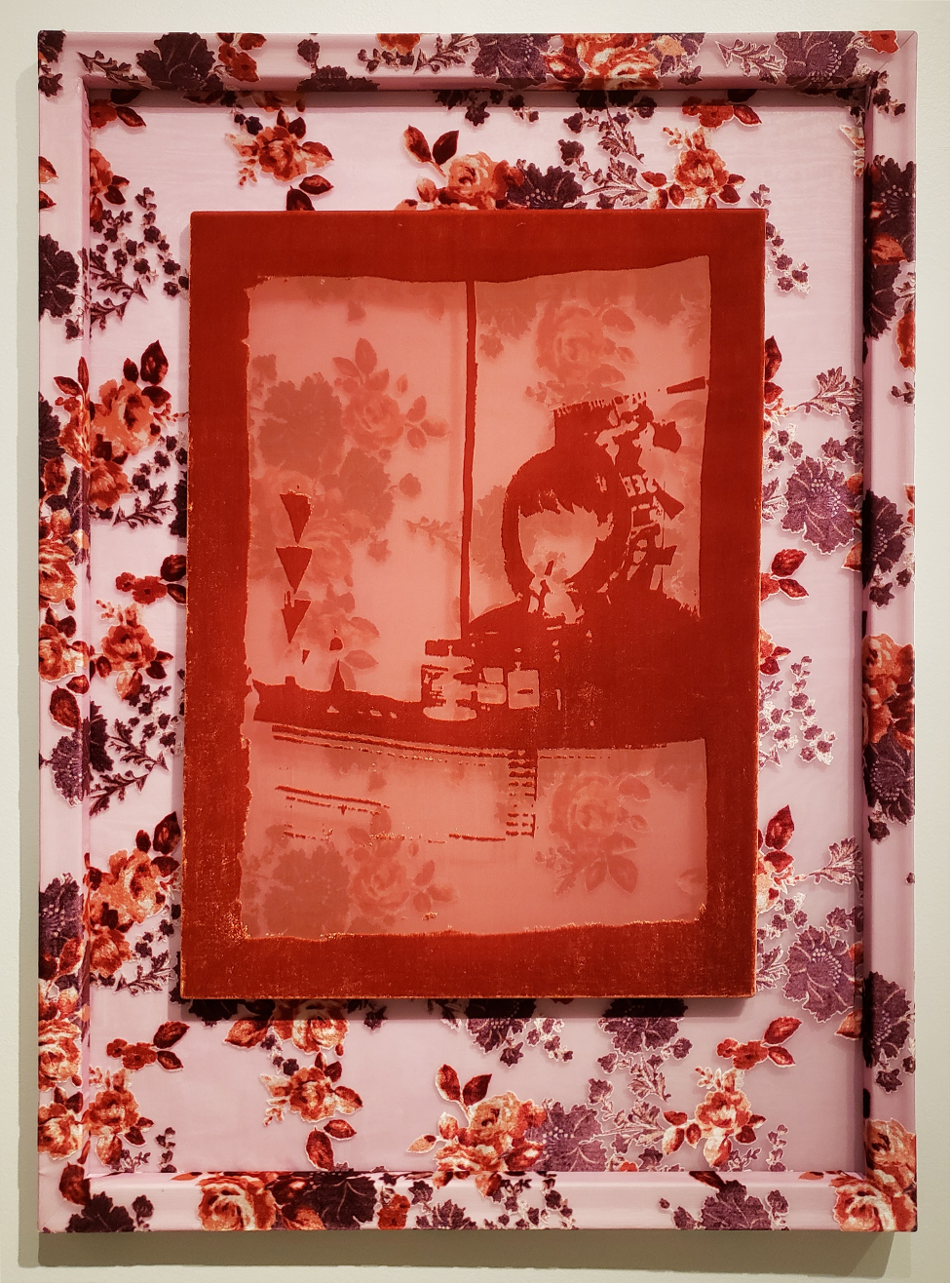 A photograph of a fiber etching made of silk and rayon depicts a young girl applying lipliner in a mirror. A bottle of Noxzema is featured in the foreground. Like the other etching featured in this series, the girl's face is missing from the image. The etching is seated in a frame that is brightly decorated with flowers.